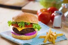 hamburger fast food with plenty of raw materials on the background - stock photo