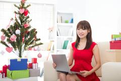 Christmas woman on laptop doing internet shopping. woman excited about buying Stock Photos