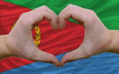 over flag of eritrea showed heart and love gesture made by hands - stock photo