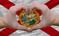 over american state flag of florida showed heart and love gesture made by han - stock photo