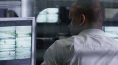 Worker in a control room is watching the screens and making a phone call - stock footage