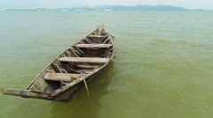 Old wooden simple fisherman boat at the shore Stock Footage
