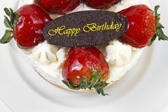 Stock Photo of butter cream cake with strawberry & birthday chocolate plate