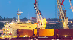 Cranes unload the ship's cargo hold timelapse at dawn Stock Footage
