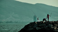 Fisherman and child silhouette on the rocks Stock Footage