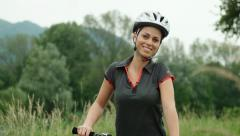 Portrait of happy young woman smiling and cycling on mountain bike Stock Footage