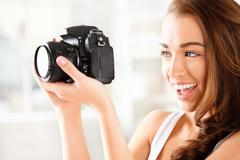 pretty woman is a proffessional photographer with dslr camera - stock photo