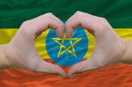 Heart and love gesture showed by hands over flag of ethiopia background Stock Photos