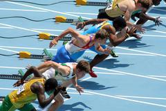 Competitors on start of 110m men hurdles - stock photo