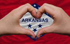 Over american state flag of arkansas showed heart and love gesture made by ha Stock Photos