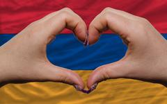 over national flag of armenia showed heart and love gesture made by hands - stock photo