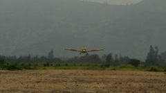 Airplane landing on dirt strip- crop duster Stock Footage