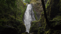 Waterfall cascades down rock face Stock Footage