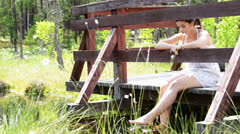 Woman sitting on bridge and relaxing - stock footage