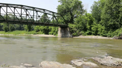Old metal bridge over flowing river in Vermont Stock Footage