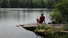 Hiker cooling his feet in a secluded mountain pond Stock Footage