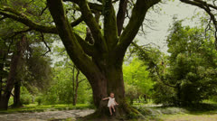 Little cute girl sits on huge fairy tree covered with moss. Concept fairy tale. Stock Footage