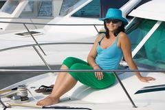Beautiful woman aboard a yacht sunbathing Stock Photos