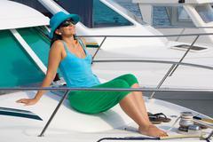 beautiful woman aboard a yacht sunbathing - stock photo