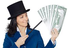 Attractive business woman with a magic wand and hat making appear giant dolla Stock Photos