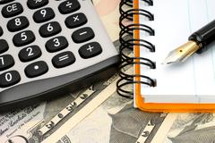 Calculator with notepad on money background close-up Stock Photos