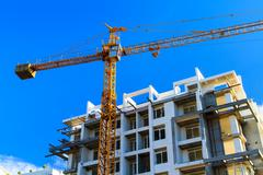 Apartments construction site with yellow crane Stock Photos