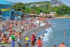alushta, ukraine - jun 01: people on the public pebble beach near black sea i - stock photo
