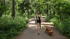 Young beautiful woman running with English Cocker Spaniel on the forest trail Stock Footage