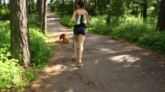Beautiful girl with English Cocker Spaniel running on the road in summer Stock Footage
