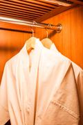 white robes with wooden hangers in hotel closet - stock photo
