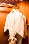 White robes with wooden hangers in hotel wardrobe Stock Photos