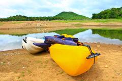 Kajakkeja, kanootti reunalla veden järvi Kuvituskuvat