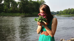 Stock Video Footage of Beautiful girl with flowers at lake river