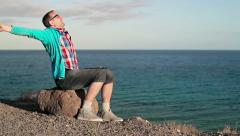 Young man relaxing on rocks near the vantage point Stock Footage