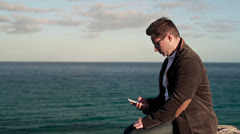 Young man sitting on rocks near the vantage point with cellphone Stock Footage