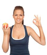 Gymnastics girl with an apple sitting saying ok Stock Photos
