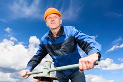Senior caucasian worker in a hardhat at the factory with the pipe valve again Stock Photos