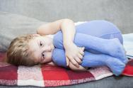 Stock Photo of little caucasian defenseless child huddled on the couch