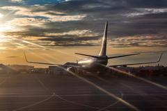 Passenger airliner riding on runway in sunset lights Stock Photos