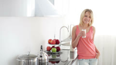 Girl standing in kitchen drinking milk with smile Stock Footage