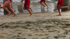 Life guards running on beach Stock Footage