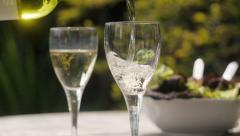 Pouring wineinto glasses al fresco, slow motion Stock Footage