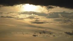Sun drops down into waves of clouds time lapse HD 1080 version Stock Footage