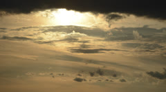 Sun drops down into waves of clouds time lapse 4K version Stock Footage