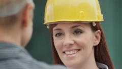 Two female architects with helmet talking and shaking hands - stock footage
