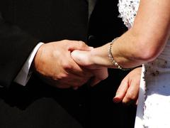 Stock Photo of Bride and groom hold hands