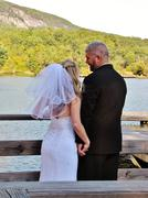Bride and groom mountain lake on dock Stock Photos