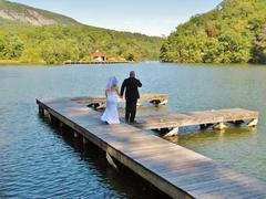 Stock Photo of Bride and groom mountain lake walking dock