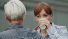 Two friendly businesswomen chat and drink during coffee break Stock Footage