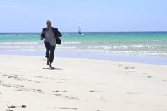 Happy businessman rasing hands to the sky on the beach, slow motion  60fps Stock Footage